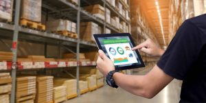 Worker hands holding tablet on blurred warehouse as background